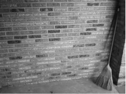 broom in corner, black and white